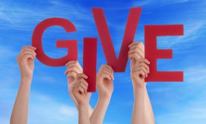 37727222 - many caucasian people and hands holding red letters or characters building the english word give on blue sky
